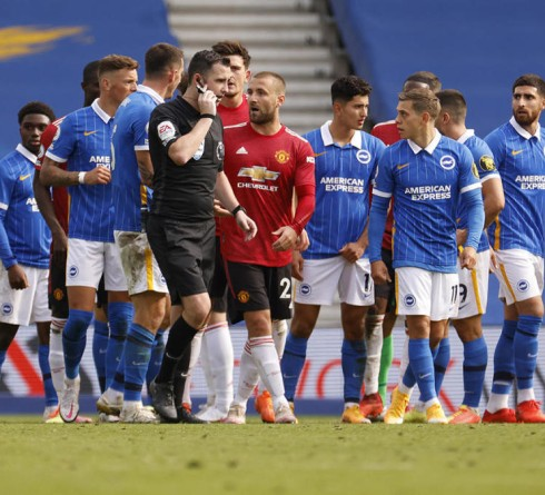 BRIGHTON, ENGLAND - SEPTEMBER 26: Luke Shaw of Manchester United talks to referee Chris Kavanagh during the Premier League match between Brighton & Hove Albion and Manchester United at American Express Community Stadium on September 26, 2020 in Brighton, England. Sporting stadiums around the UK remain under strict restrictions due to the Coronavirus Pandemic as Government social distancing laws prohibit fans inside venues resulting in games being played behind closed doors. (Photo by John Sibley - Pool/Getty Images)