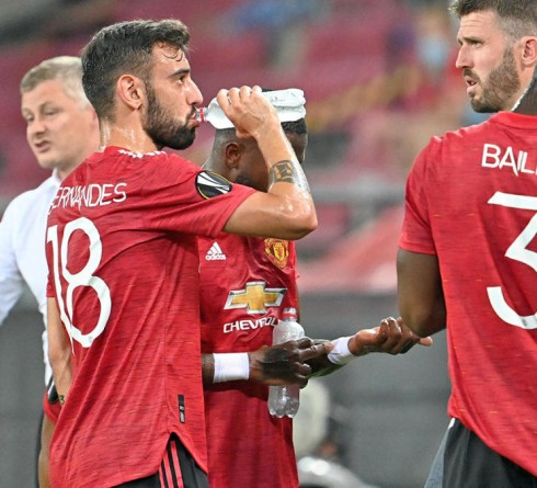 10 August 2020, North Rhine-Westphalia, Cologne: Football: Europa League, Manchester United - FC Copenhagen, Final-Eight, quarter-finals at the Rhein-Energie-Stadium. Bruno Fernandes (2nd from left), Fred (undercover), David de Gea and Eric Bailly from Manchester talk to each other during a drinking break, while coach Ole Gunnar Solskjaer (left) gives instructions. Photo: Federico Gambarini/dpa (Photo by Federico Gambarini/picture alliance via Getty Images)